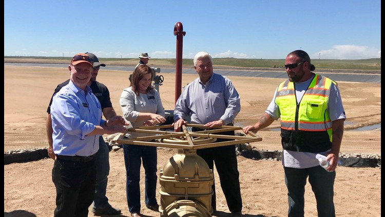 Colorado Treasurer Dave Young helps turn the wheel to allow water into the 70 Ranch Reservoir.