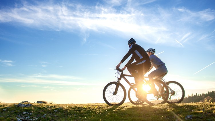 Happy mountain bike couple outdoors have fun together on a summer afternoon sunset. biking cycling summer mountains