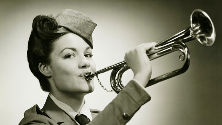 Young woman in soldiers uniform playing on bugle