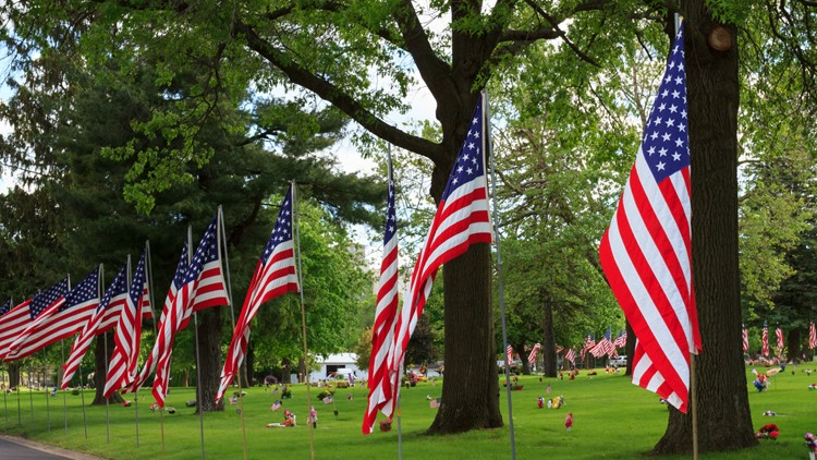 A row of American flags on the side of a road honoring fallen soldiers in a cemetery on Memorial Day