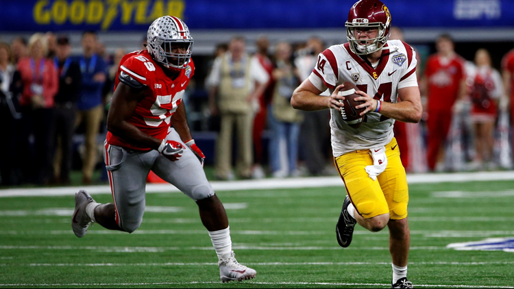 Sam Darnold runs from Tyquan Lewis #59 of the Ohio State Buckeyes in the second half of the 82nd Goodyear Cotton Bowl Classic between USC and Ohio State at AT&T Stadium on December 29, 2017. Photo by Ron Jenkins/Getty Images.