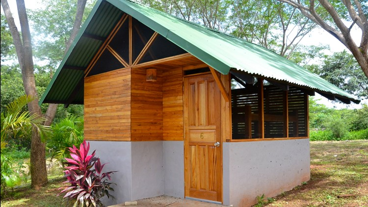 A tiny cabin cottage at a tropical retreat among trees and plants. This wood and concrete bunk house features a green tin roof, wooden doors and walls, screened in windows, and a concrete base. This tiny house is the type of structure you might find at a lodge or resort.