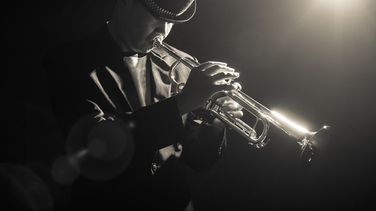 Musician playing the Trumpet with spot light and len flare on the stage jazz festival