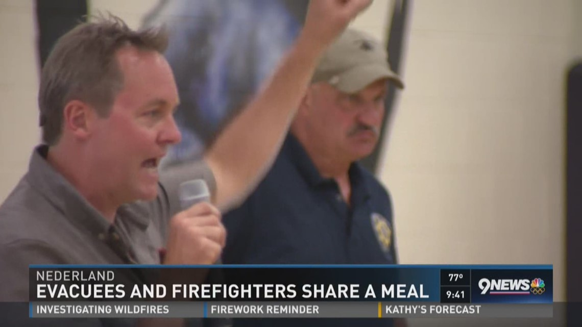 Evacees and firefighters share a meal