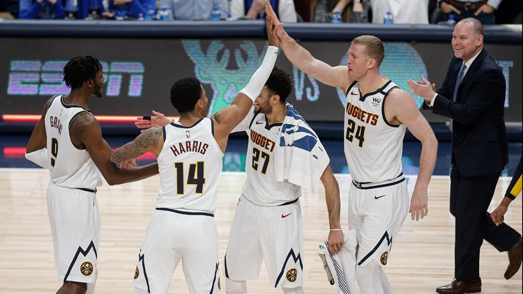 Denver Nuggets' Jerami Grant (9), Gary Harris (14), Jamal Murray (27) and Mason Plumlee (24) celebrate the team's 107-106 win over the Dallas Maverick
