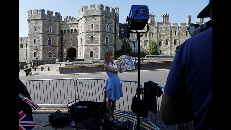 A television reporter for the US network CNN, holds up copies of today's British newspapers leading with a story of Meghan Markle's father Thomas Markle, opposite the Henry VII Gate of Windsor Castle in Windsor, west of London on May 15, 2018