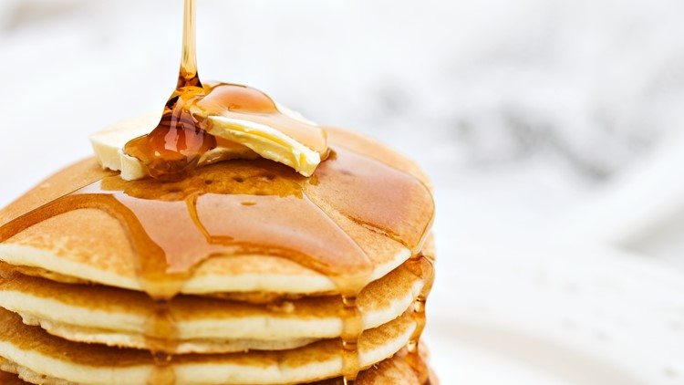 Maple syrup pouring onto pancakes. Shallow DOF with focus on syrup and butter.