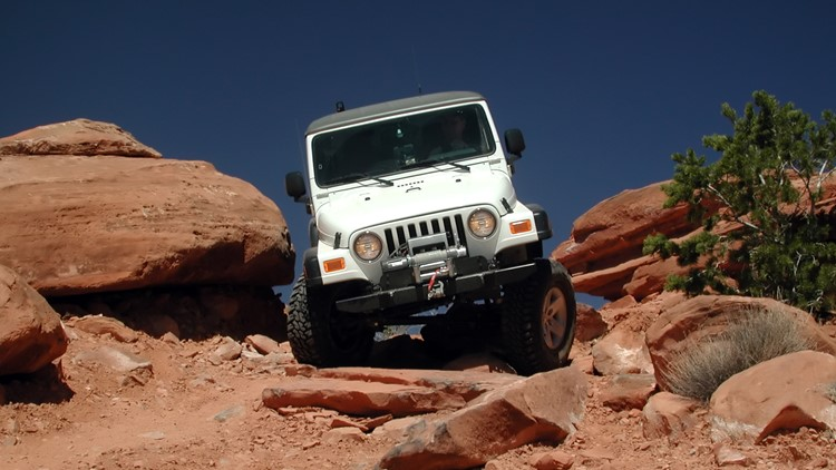 Jeep Rubicon offroad on Flat Iron Mesa trail near Moab, Utah.