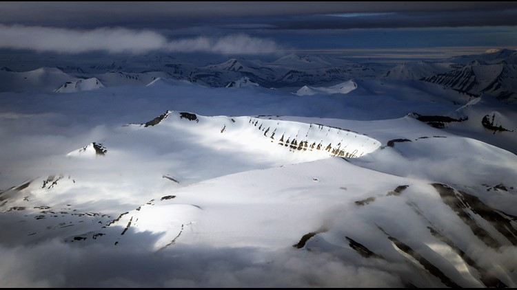 LONGYEARBYEN, NORWAY - JUNE 21: Mist encircles mountain peaks as the midnight sun reflects off the face of ridges on the West Coast of Spitsbergen early in the morning of Midsummer on June 21, 2008 in Longyearbyen, Norway.