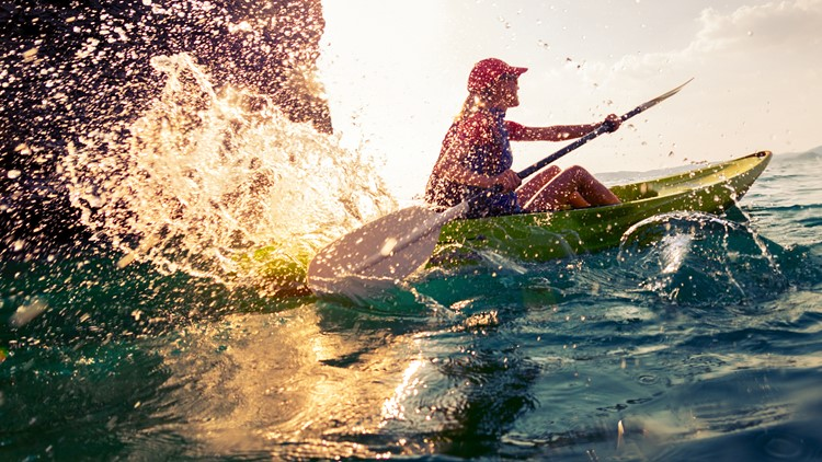 Young lady paddling hard the sea kayak with lots of splashes yakak yakaking