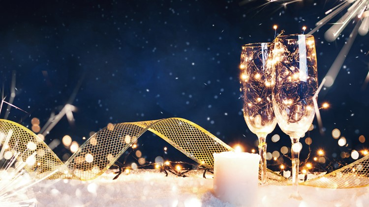 Two glasses filled with garlands with a candle and a gold ribbon in the snow. Christmas card new year's eve event paraty