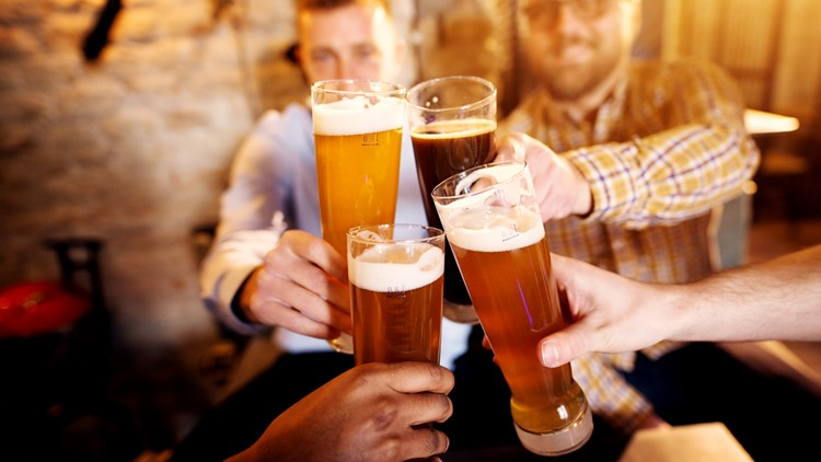 A group of young men clinking glasses with a beer in the sunny pub drinking beer festival