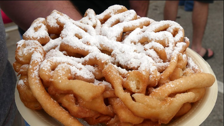 A hand holding a plate of funnel cake with powdered sugar on top