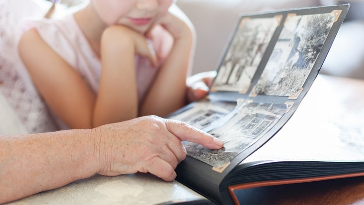 Grandmother and granddaughter watching old photo album at home. Senior woman shows child black and white photos. Hands of retired person and kid. Family leisure.