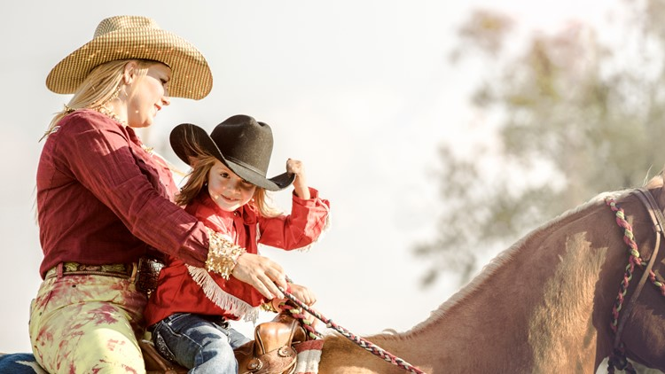 An adorable little girl tips her hat while riding a horse at a rodeo