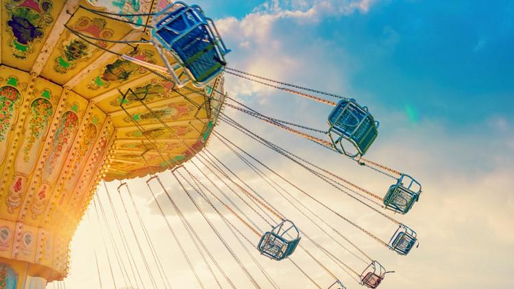 Summer Carnival Tilt-a-while amusement park ride festival swinging carousel fair ride at dusk