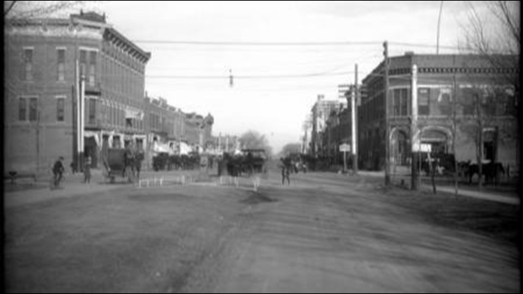 View of street in downtown Greeley, Colorado; livestock drinking or water fountain in middle of intersection, Park Place building, numerous horse-drawn carriages and wagons, early automobiles, and other brick buildings in town.
