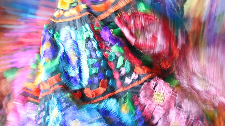 The bright colors of a traditional Mexican dress are intentionally blurred to show the movement and speed of the dancing.