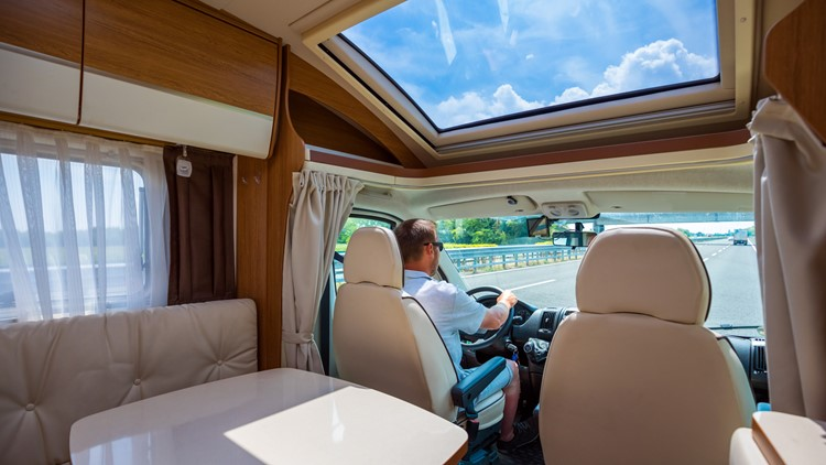 Man driving on a road in the Camper Van RV.  RVs rv show motorhome vacation