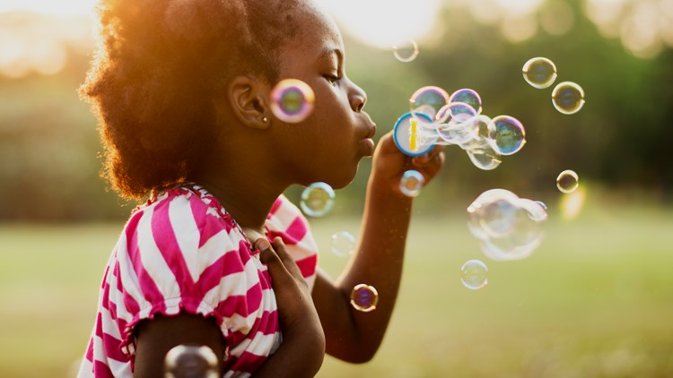 African descent girl playing blowing bubbles