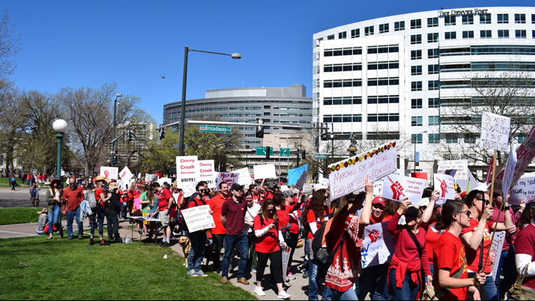 Teachers march on the sidewalk along Colfax Avenue on Friday.
