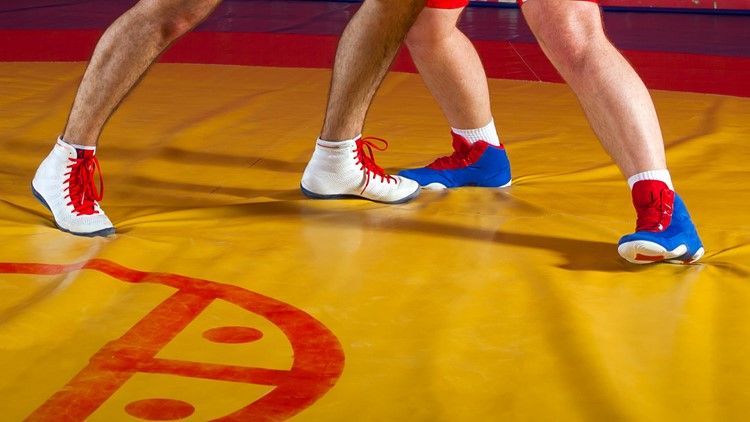 Two strong wrestlers in blue and red wrestling tights are wrestlng on a yellow wrestling carpet in the gym.