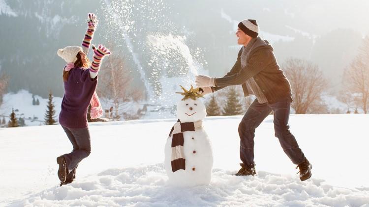Couple making snowman winter festival snow