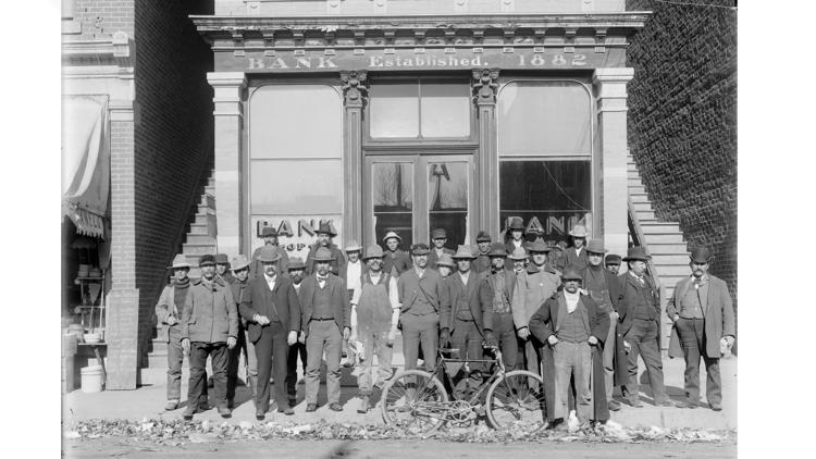 A group of men pose on the sidewalk in front of the Bank of Loveland, established in 1882