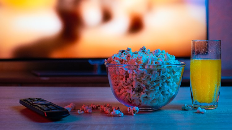 Popcorn in a glass plate with a drink on the background of the TV. Color bright lighting. Background