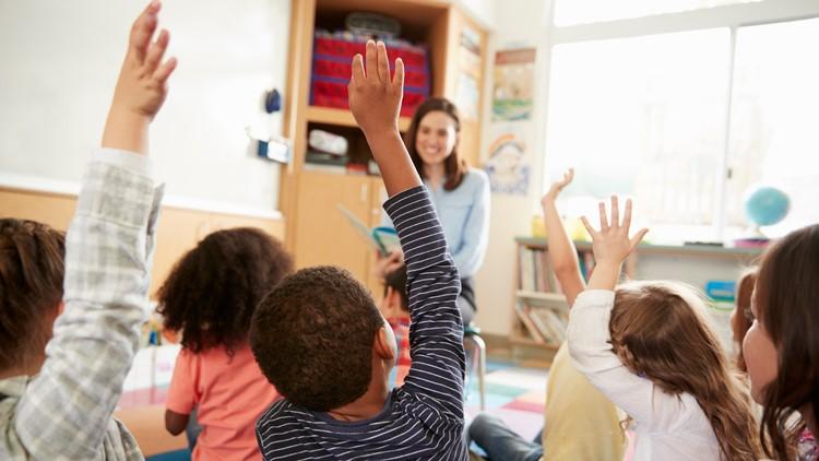 Elementary school kids raising hands to teacher, back view teachers school teaching