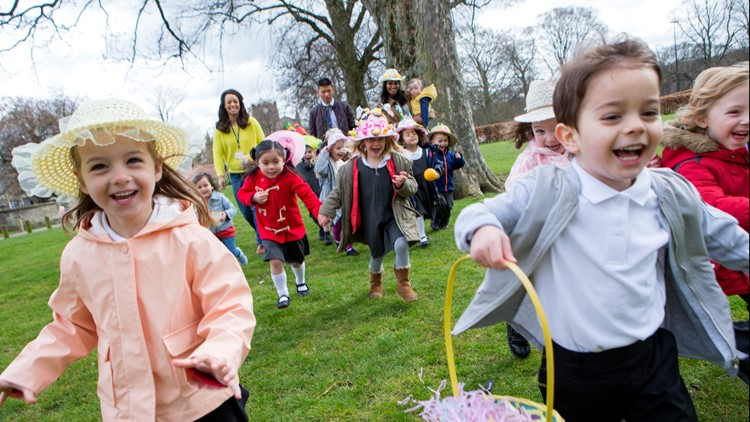 Nursery children running across a field during their outdoor Easter egg hunt, they are wearing handmade hats and carrying baskets eggs
