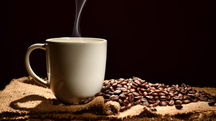Cup of coffee with smoke and coffee beans on black background coffee festival generic
