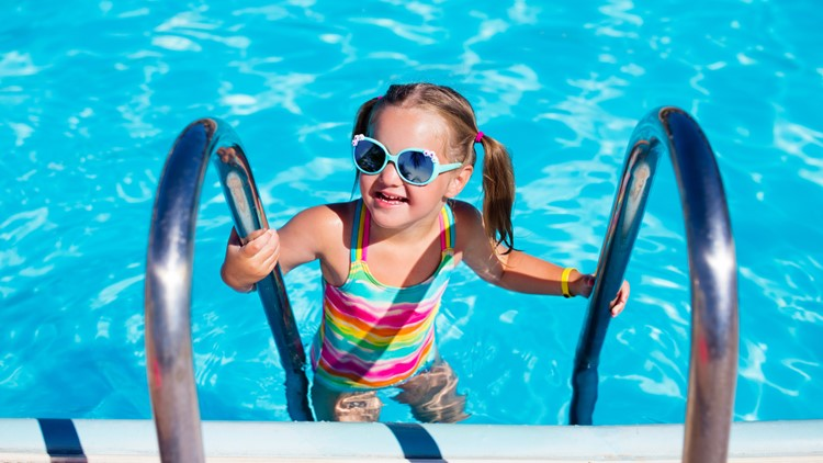 Happy laughing little girl playing in outdoor swimming pool on a hot summer day. Kid in colorful bathing suit and goggles learning to swim in tropical resort. Water fun for children.