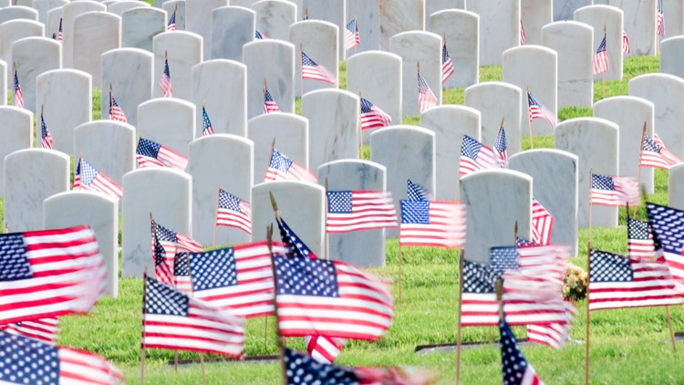 American Flags waving in the breeze in a cemetery memorial day flag placing