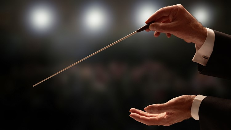 Conductor conducting an orchestra with audience in background opera