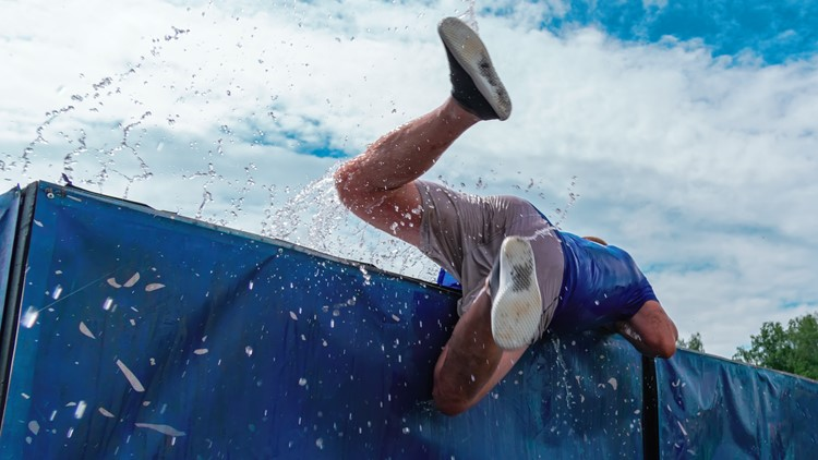 Low angle view of man getting out of the water obstacle against sky during an extreme mud obstacle race. Rear view.