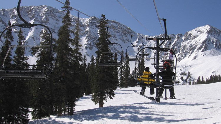 A high mountain ski lift carrying skiers and snowboarders at Copper Mountain, Colorado.