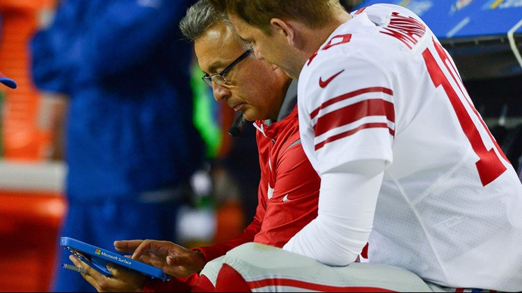 DENVER, CO - OCTOBER 15: Offensive coordinator Mike Sullivan reviews game footage on a Microsoft Surface with Eli Manning #10 during the second quarter of a game against the Denver Broncos at Sports Authority Field at Mile High.