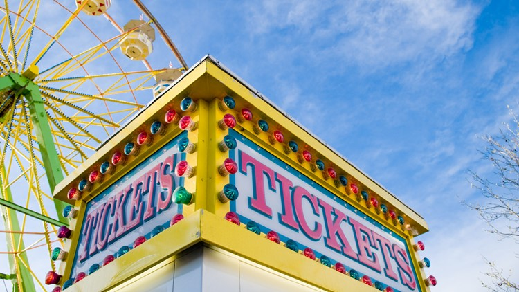 Tickets sign at county fair with Ferris wheel and light colored blue sky with white clouds in the background. carnival fair