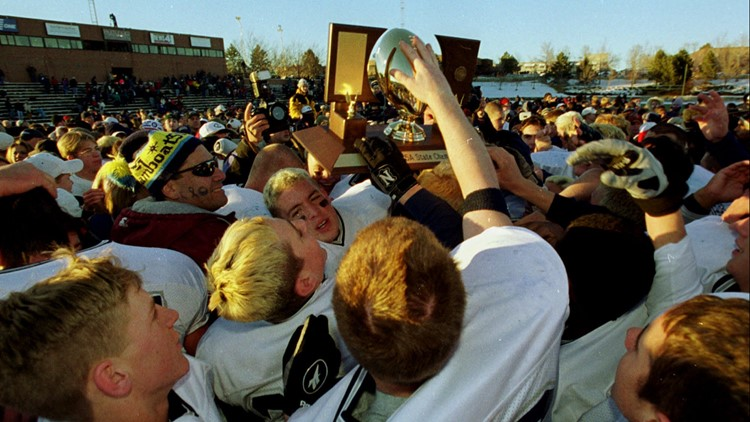 Members of Columbine High School's football team reach over each other to touch the Class 5A state championship trophy after Columbine's 21-14 victory over Cherry Creek High School to win the crown Saturday, Dec. 4, 1999, in the Stutler Bowl in Englewood, Colo.