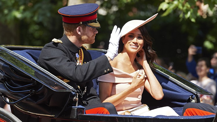 Britain's Prince Harry, Duke of Sussex and Britain's Meghan, Duchess of Sussex travel in a horse-drawn carriage down The Mall to Horseguards parade ahead of the Queen's Birthday Parade, 'Trooping the Colour', in London on June 9, 2018.